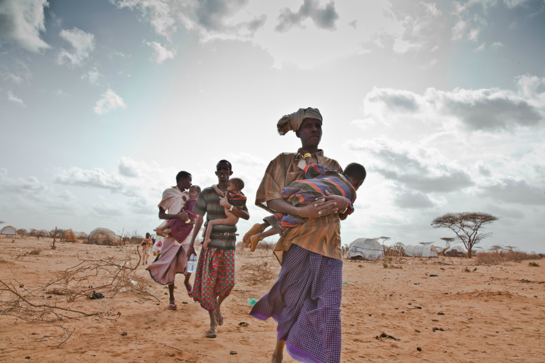 Somali refugees in Dagahaley refugee camp carrying their sick and malnourished children to a new feeding center run by Doctors Without Borders on the outskirts of the sprawling refugee camp in Kenya. Image:brendanbannon.com
