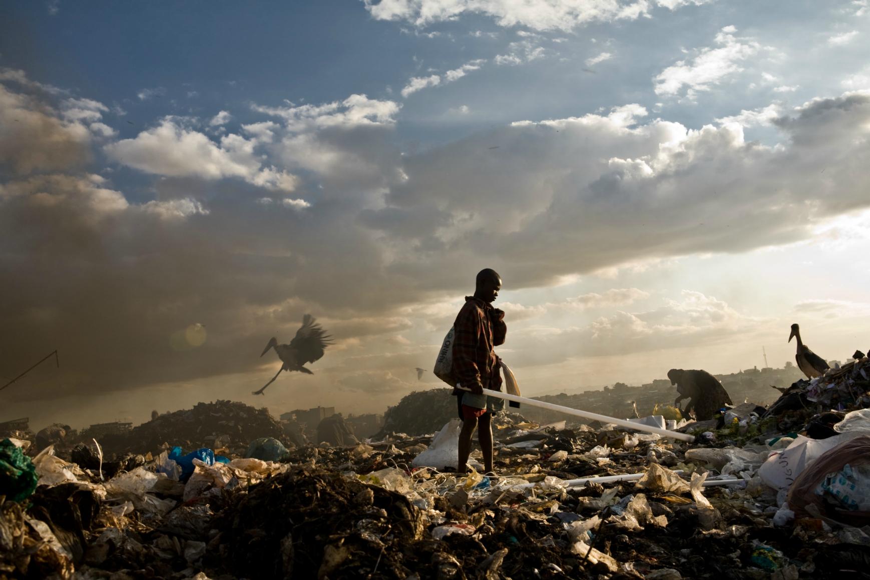 A young boy scavenging florescent light tubes in Kenya's Dandora dump site. Image:brendanbannon.com