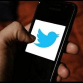 hand holding smartphone with Twitter logo on screen