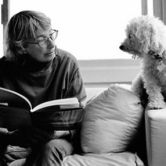 The poet Mary Oliver looking at a white dog