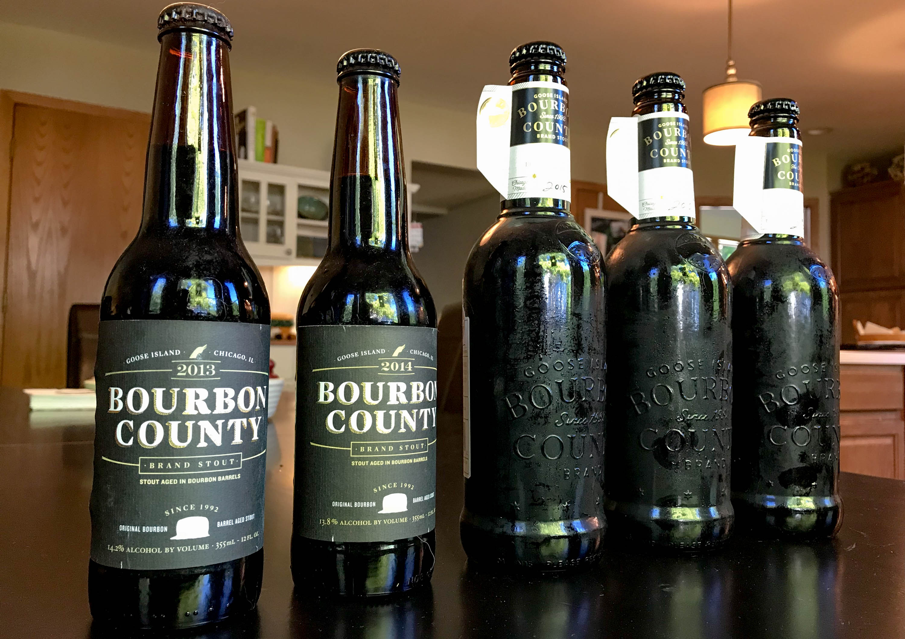 A five year vertical of Bourbon County Brand Stout. Older, pre-brewery sale style bottles are on the left, while the newer bottle design is on the right. <em>Michael Neelsen (TTBOOK)</em>