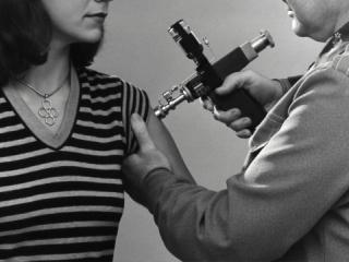 """Created in 1976, this historic photograph showed an adult female receiving a vaccination that was administered by a public health clinician, by way of a jet injector, also known as a """"Ped-O-Jet®"""", during the nationwide Swine Flu vaccination campaign"""
