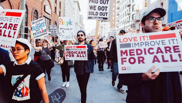 "Demonstrators march for ""Medicare for All"" and other socialist-leaning policy goals."