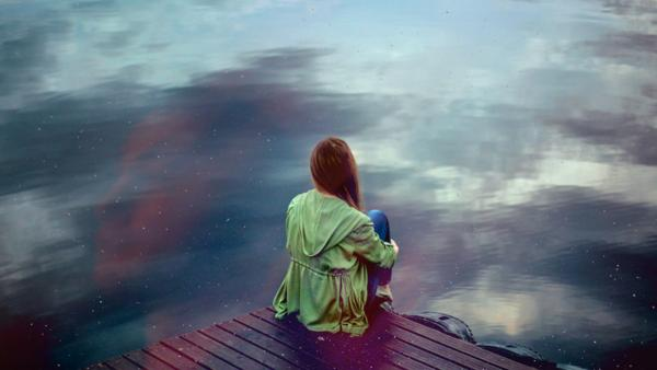 Woman gazing upon a lonely, infinite shore