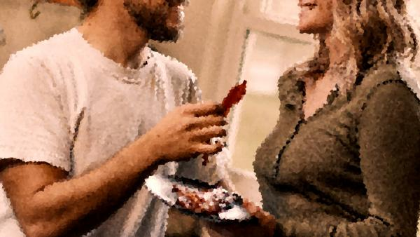A man and woman share a plate of bacon.