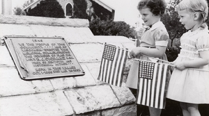 Two young girls hold American flags next to a plaque honoring Bernard J. Cigrand in Waubeka