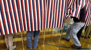 People voting behind a curtain