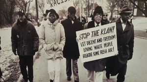 A photo at the exhibit shows James Cameron marching with a sign opposing the Ku Klux Klan.