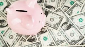 Image of piggy bank atop one dollar bills