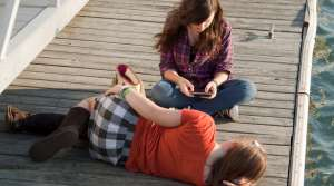 Girls sitting on a pier