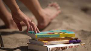 Stack of books next to a person on the beach