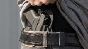 Gun in holster with person's hand