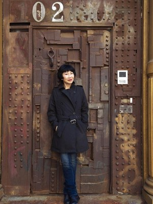 Amy Tan stands in front of a riveted metal door