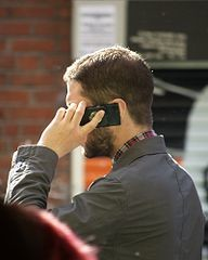 man on cell phone, image by Wikimedia user Tim Parkinson