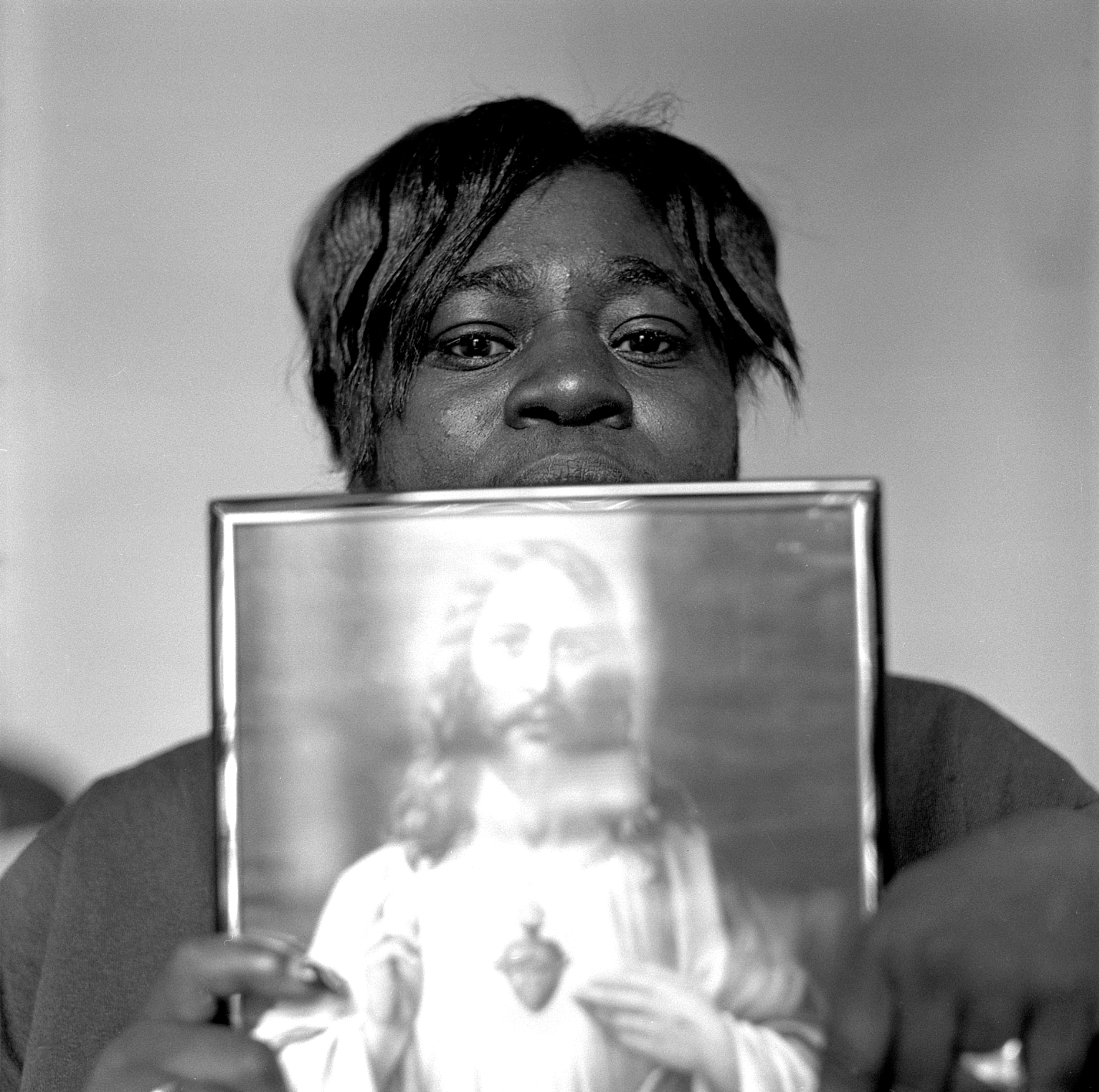 A client of Miriam's house, a residential home for women with AIDS, showing a picture of Christ as a sign what is keeping her strong, Washington, D.C.,1997