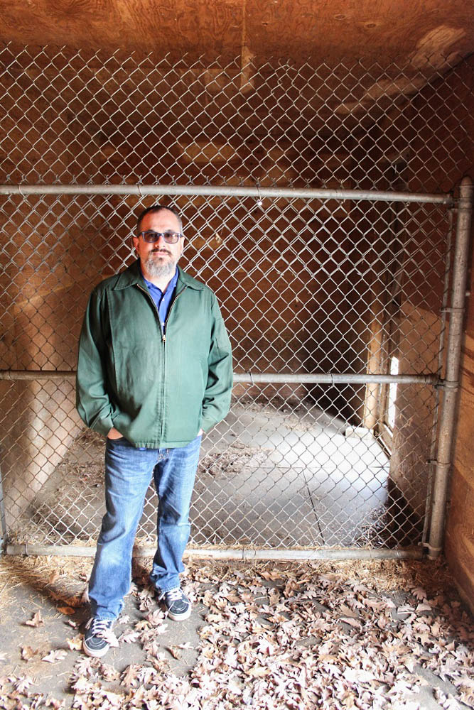 TTBOOK producer Charles Monroe-Kane standing in one of the tiger cages of Mike Tyson's abandoned mansion in Southington, Ohio. <em>Seth Jovaag (TTBOOK)</em>
