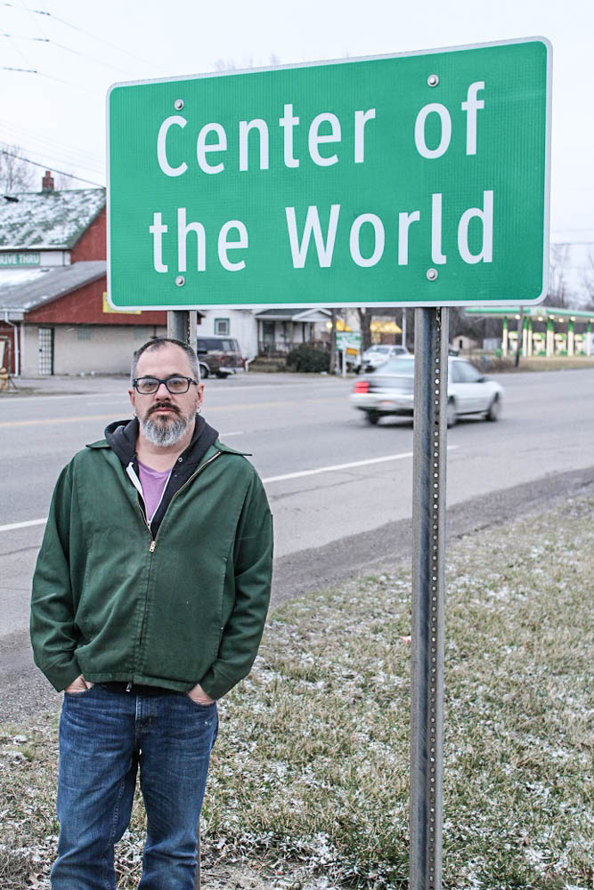 TTBOOK producer Charles Monroe-Kane at the Center of the World sign. The sign is a stone's throw from his parent's now abandoned home. <em>Seth Jovaag (TTBOOK)</em>