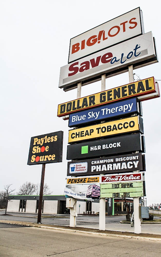 Once the site of more high-end stores, the nearby strip mall is filled with what residents can afford - discounts. <em>Seth Jovaag (TTBOOK)</em>