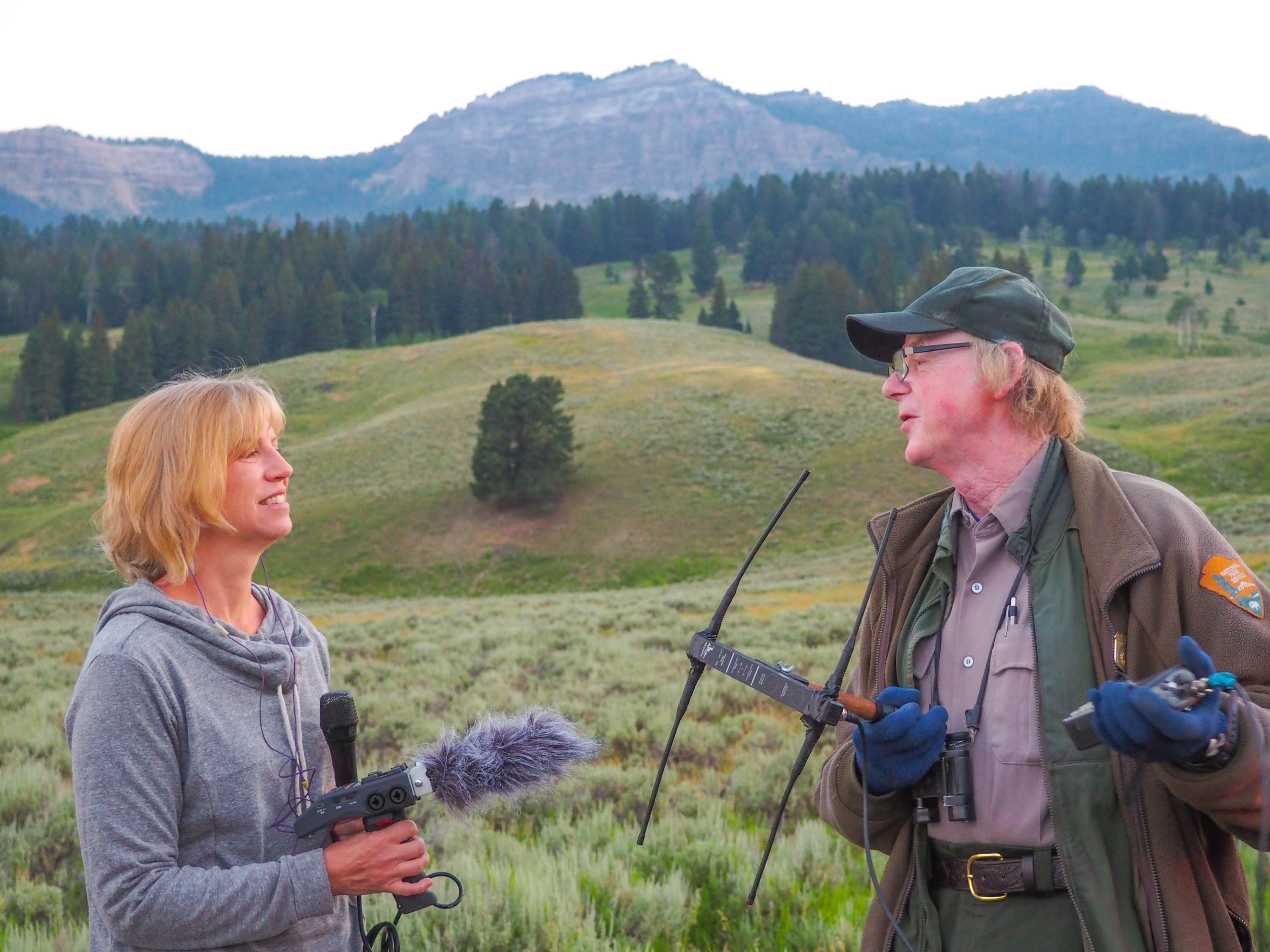 Anne interviews Rick McIntyre during a wolf watching session. <em>Steve Paulson (TTBOOK)</em>