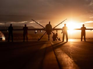 Airmen pose with an MQ-9 Reaper at Creech Air Force Base.