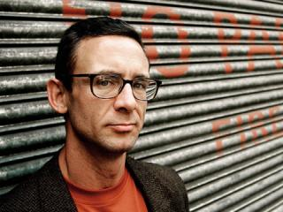 Chuck Palahniuk standing in front of a corrugated iron wall