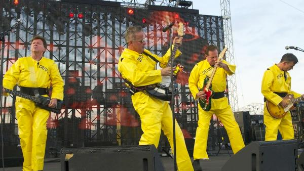 Devo performing live at the Forecastle Festival, in Louisville, Kentucky, 2010 Left to right: Gerald Casale (bass), Mark Mothersbaugh (vocals; keyboards), Bob Casale (keyboards; guitar), and Bob Mothersbaugh (guitar)