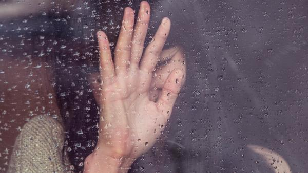 Touching glass in a rainstorm