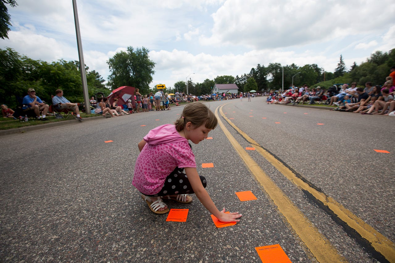young girl placing road apple sticker on pittsville fourth of july parade route