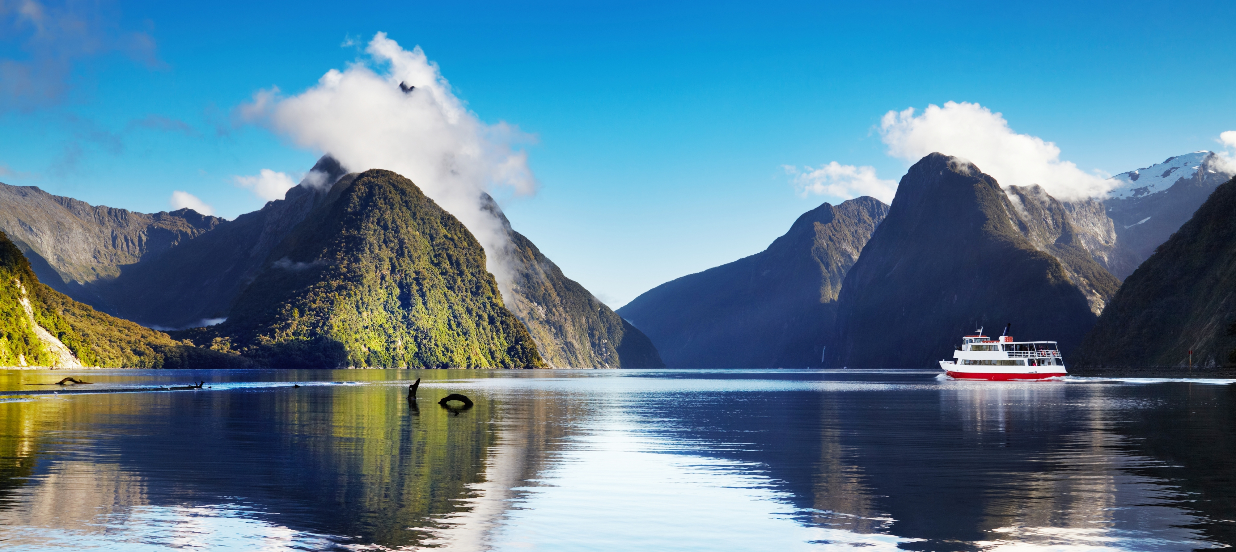 ferry on smooth water of Milford Sound with mountains in the background