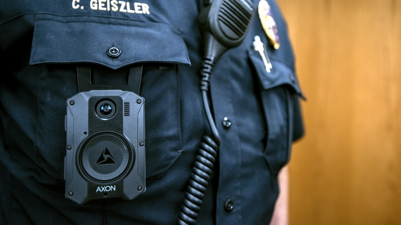 A body camera is clipped onto the pocket of a police officer's uniform.