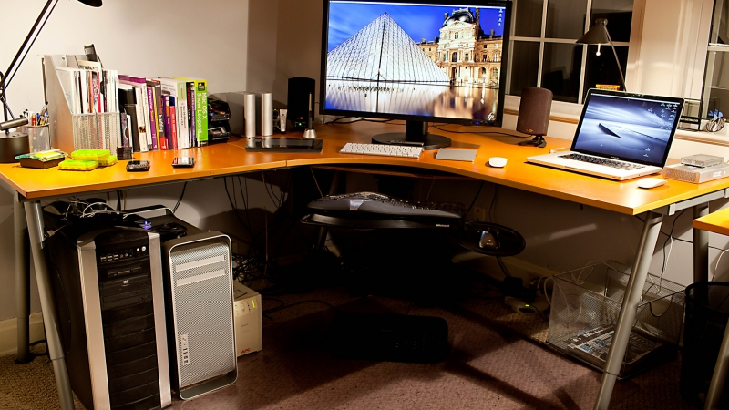 A large corner desk with books, computer screen and laptop on the top and two modems underneath.