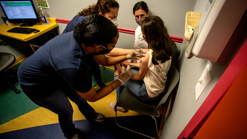 Middle school student Elise Robinson receives her first coronavirus vaccination
