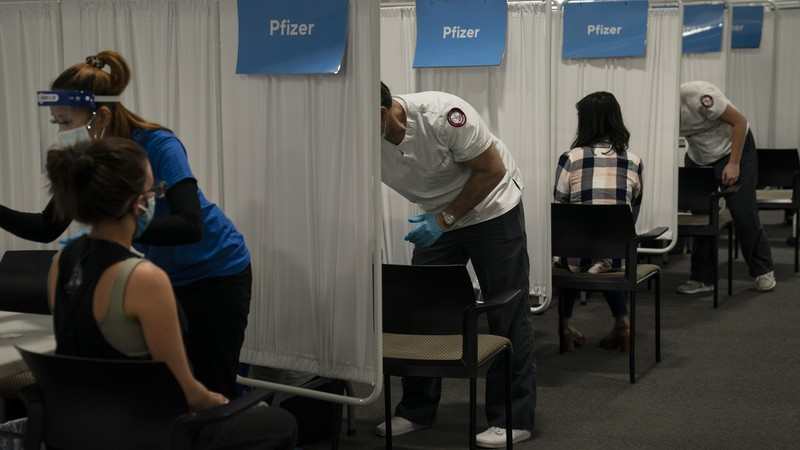 student nurse Dario Gomez disinfects a chair after administering the Pfizer COVID-19 vaccine