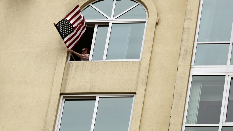 Woman holds flag out a window in quarantine