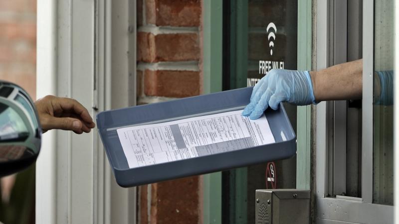 employee hands unemployment paperwork to resident