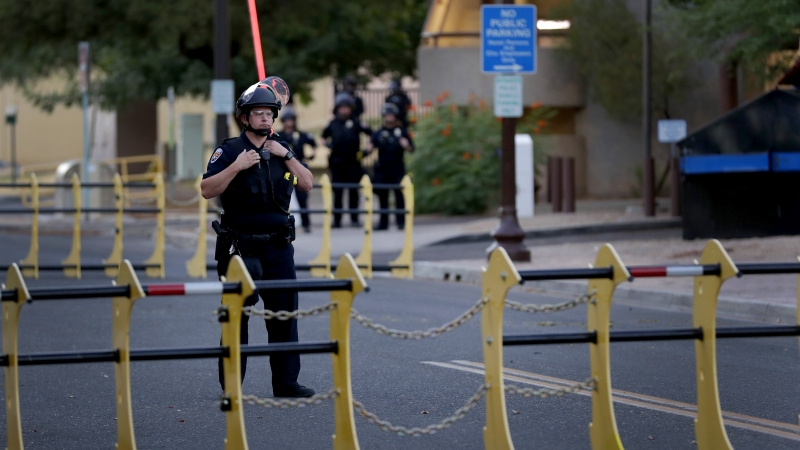 A police officer stands behind a barricade