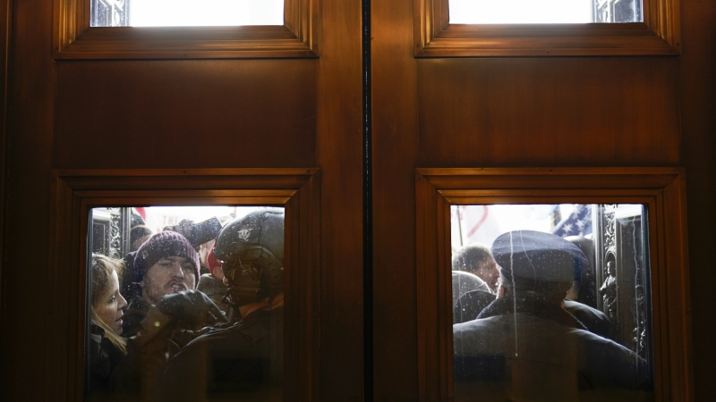 U.S. Capitol Police try to hold back a mob of Trump supporters outside the east doors to the House side of the U.S. Capitol.