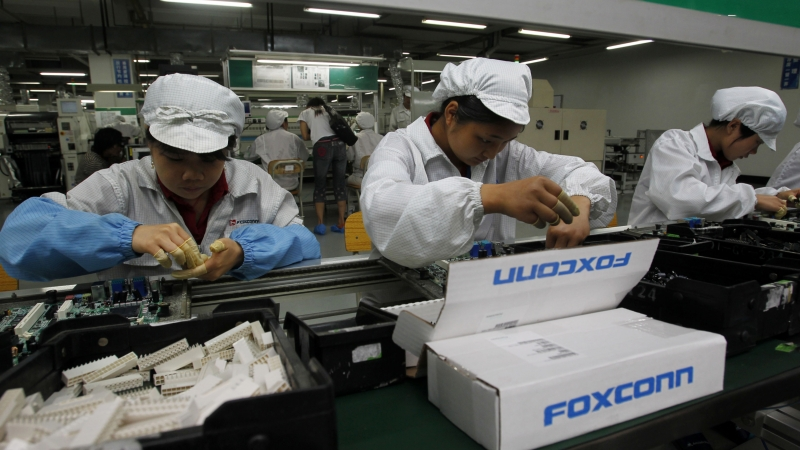 Employees work on the production line at the Foxconn complex in the southern Chinese city of Shenzhen, southern China