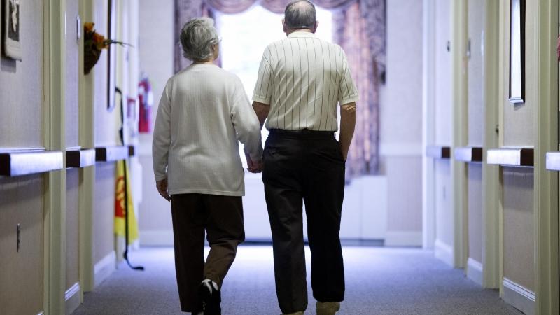 Couple walking through the hallway of a nursing home