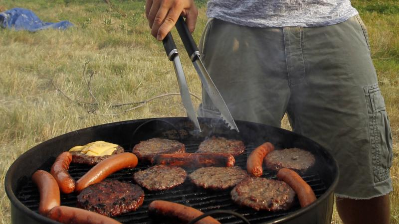 Person grilling hamburgers and hotdogs