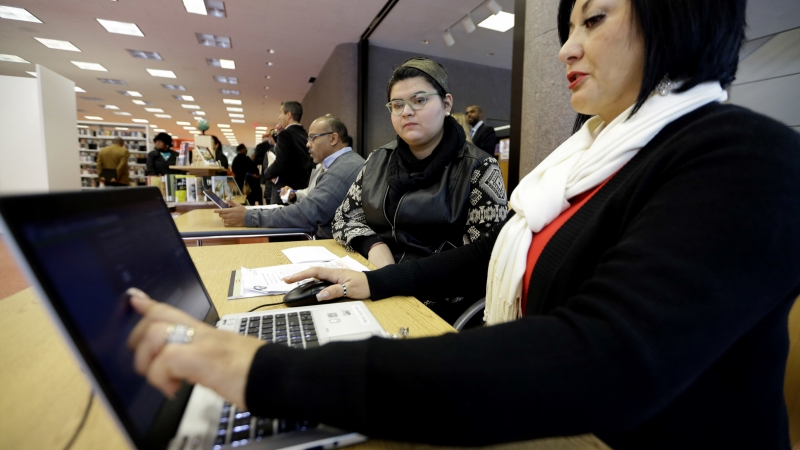 ACA health insurance marketplace navigator Leticia Chaw, right, helps gather information for Jennifer Sanchez to re-enroll in a health insurance