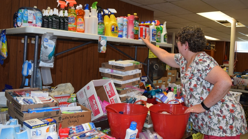 Joan Hollendyke straightens donated cleaning supplies