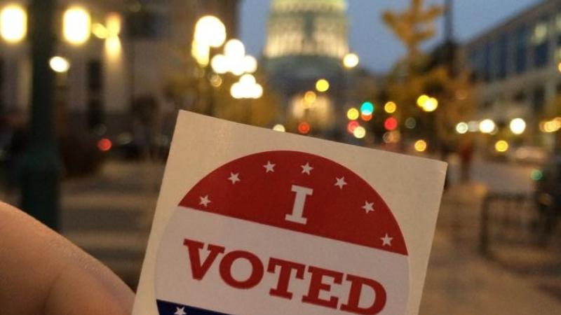 """""""I Voted Today"""" sticker held in front of the Wisconsin state capitol"""