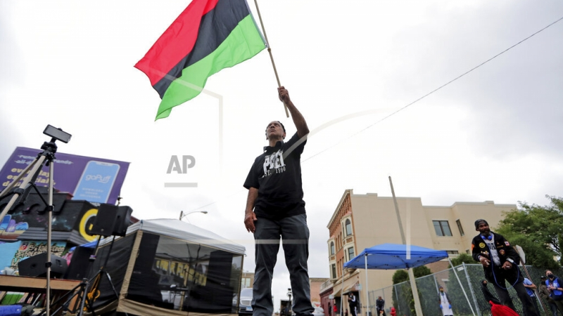 Duncan Ellington waves an African flag during a protest rally for Jacob Blake
