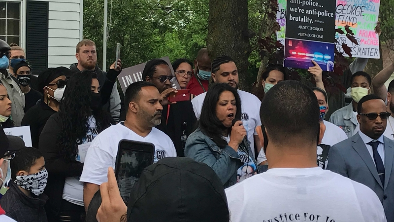 A woman with a microphone speaks to a crowd holding signs outside a home