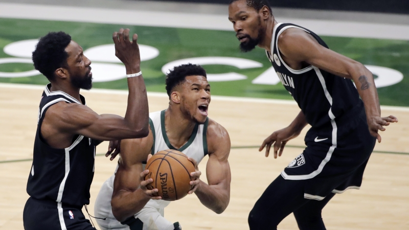 Giannis Antetokounmpo maneuvers between two Nets players