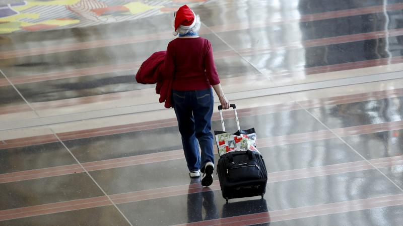 woman A woman in a Santa hat rolls her luggage through airport