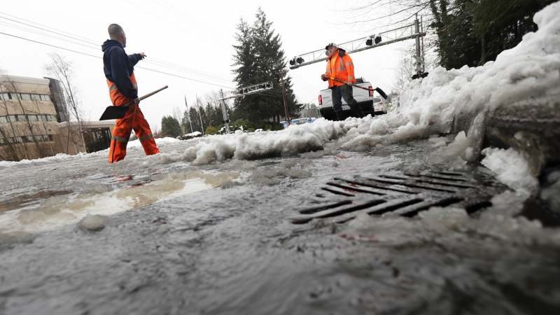 workers clear melting snow from a street drain