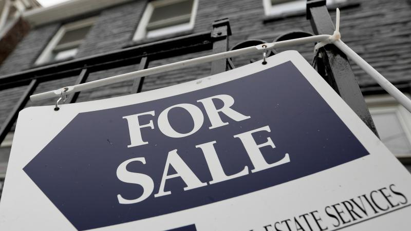 a sign is displayed outside a house for sale