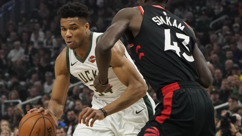 Milwaukee Bucks' Giannis Antetokounmpo tries to drive past Toronto Raptors' Pascal Siakam